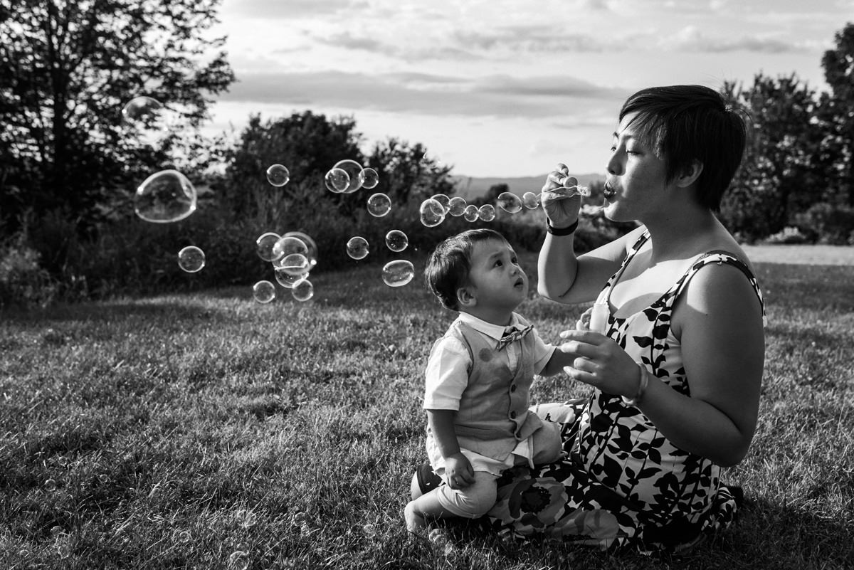 Wedding guest blowing bubbles for her toddler