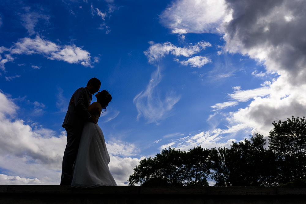 Silhouette of wedding couple against the blue sky