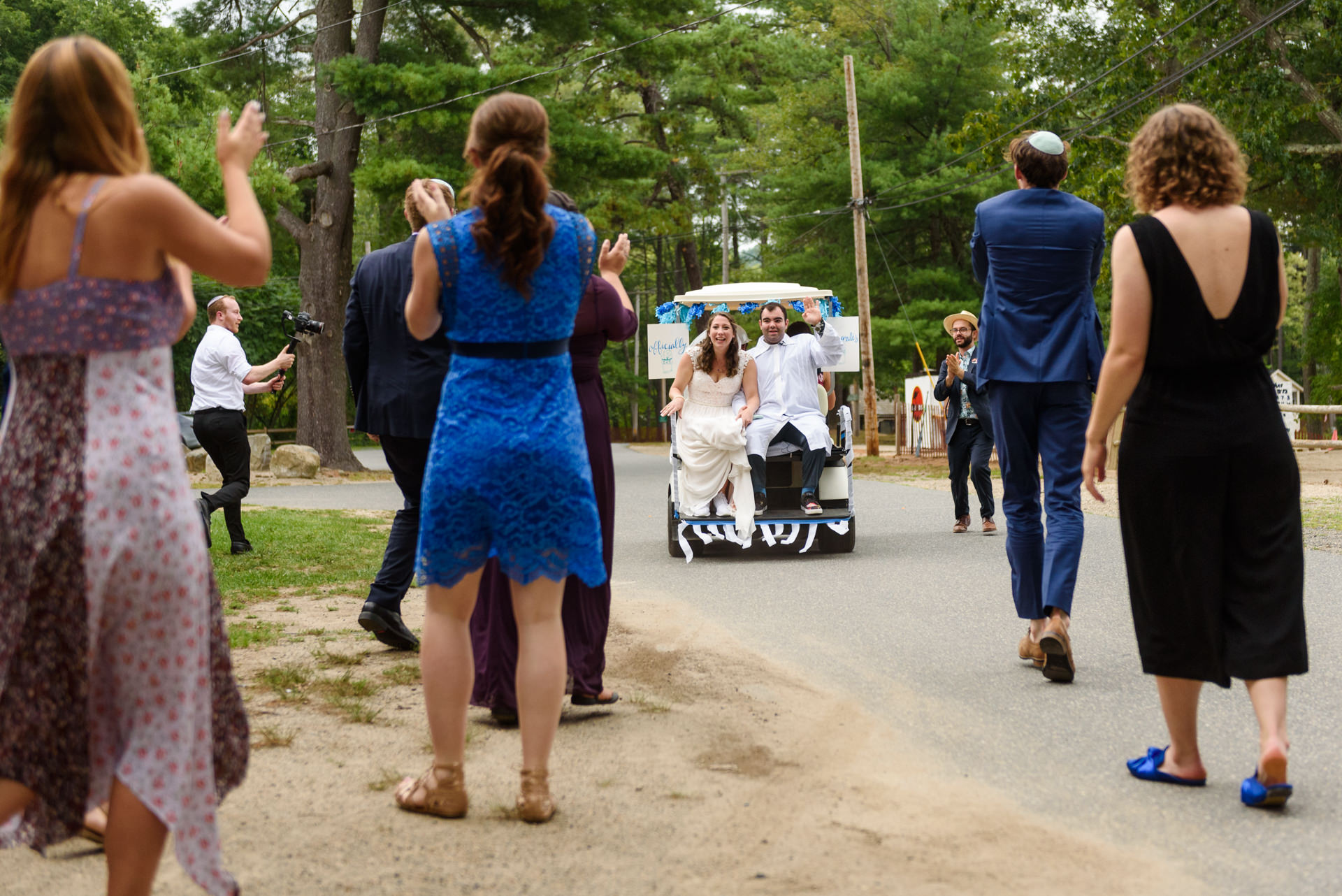 Bride and groom exiting in a golf cart