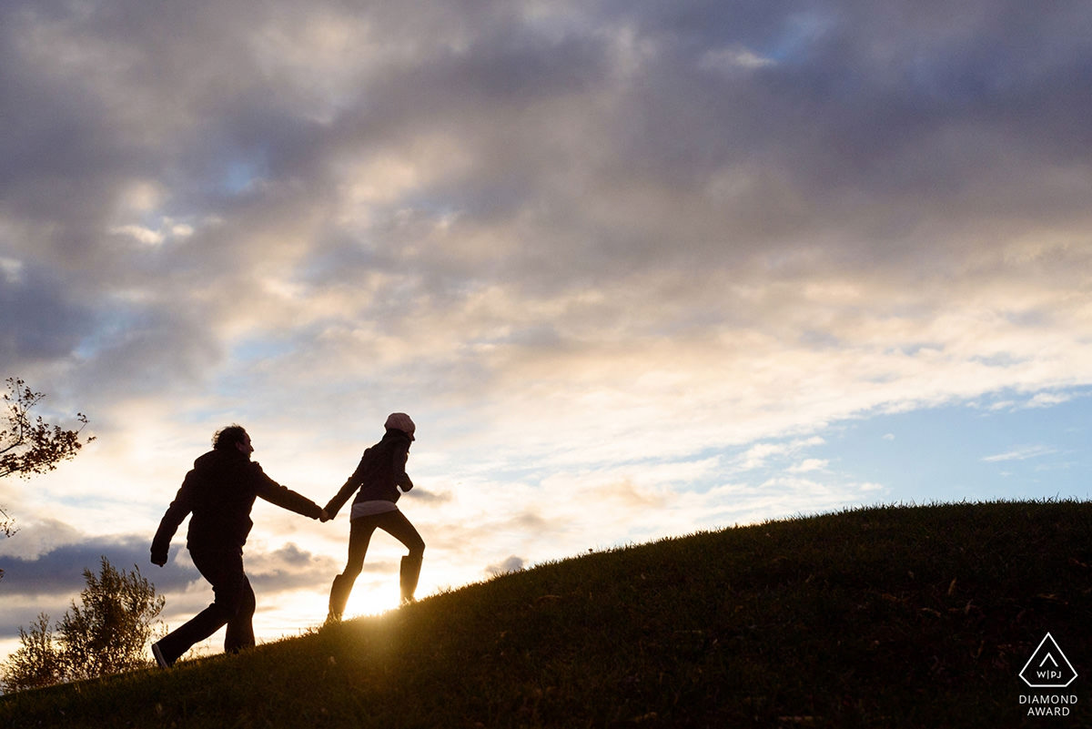 Award-winning engagement photo of couple running uphill in the sunset