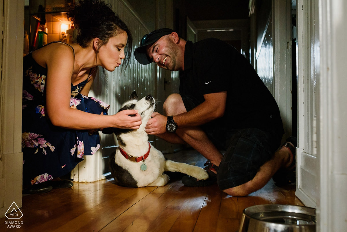 Award-winning engagement photo of couple at home with their pet husky