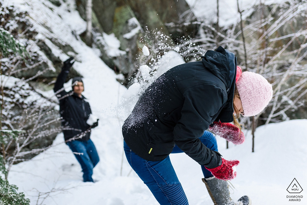 Award-winning engagement photo of couple having a snowball fight