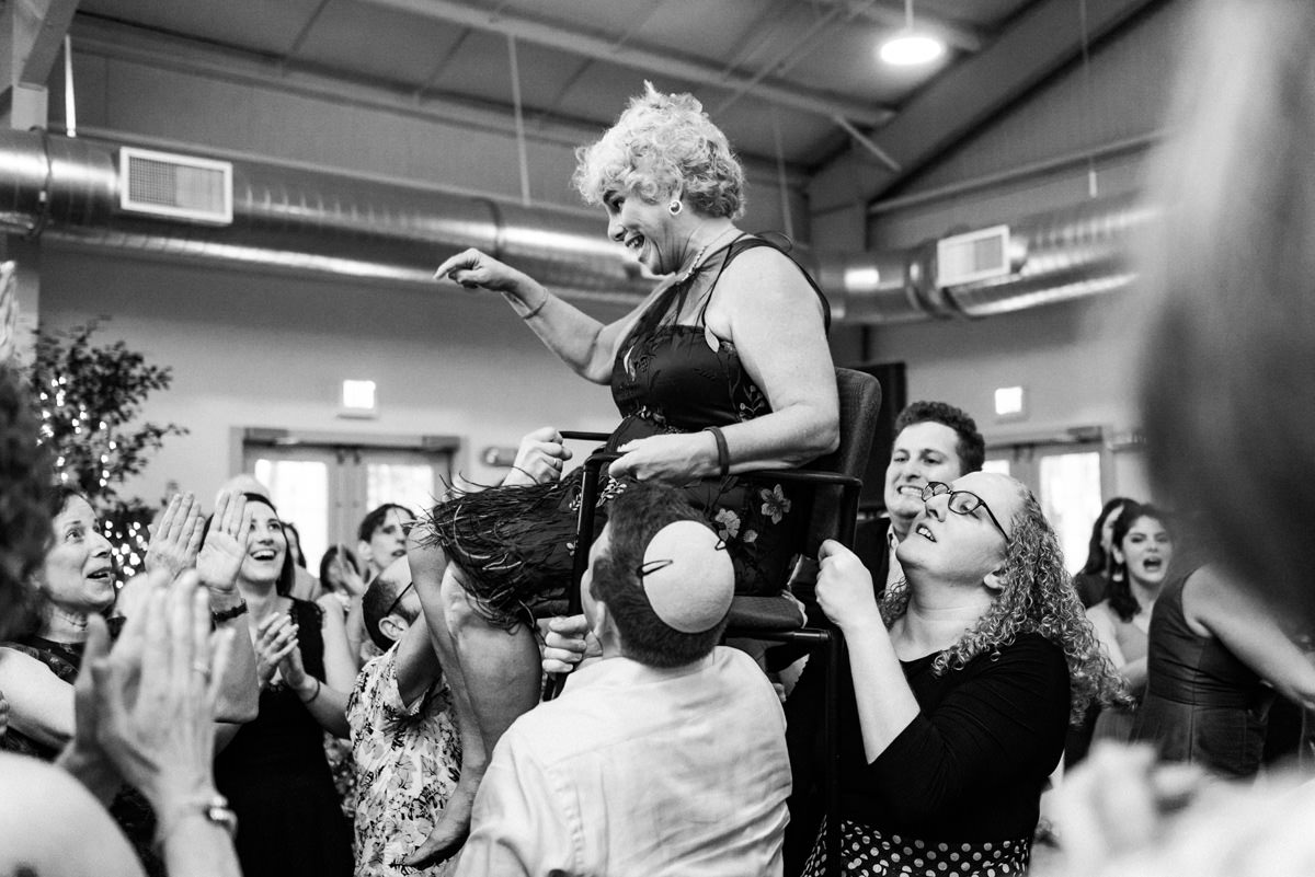 Mother of the groom being lifted on chair in Massachusetts wedding