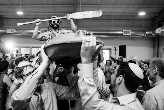 Wedding guest crowdsurfing in a kayak during wedding reception