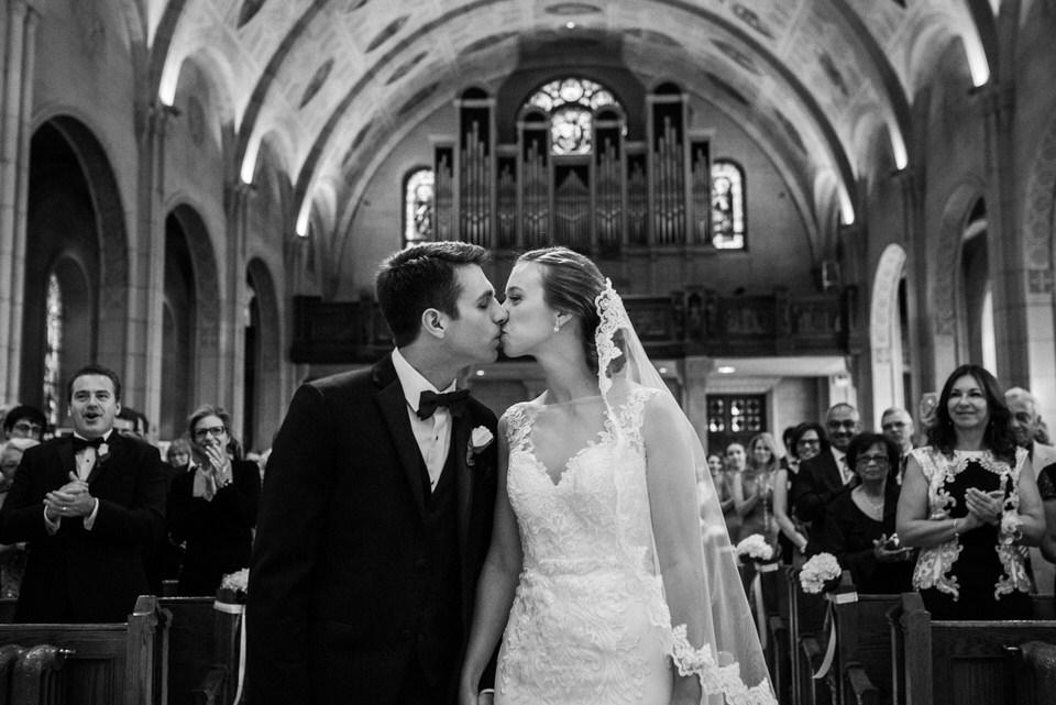 Wedding couple kissing during catholic ceremony