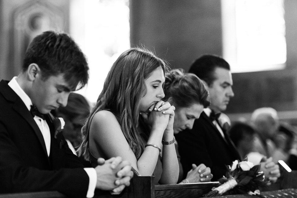 Guests praying at wedding
