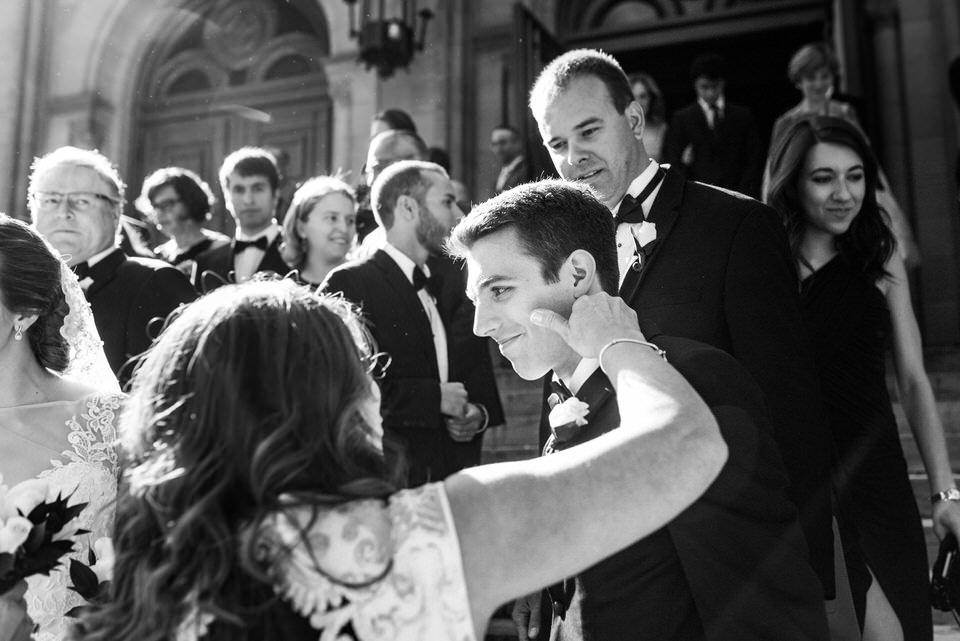 Mom pinching groom's cheeks after wedding