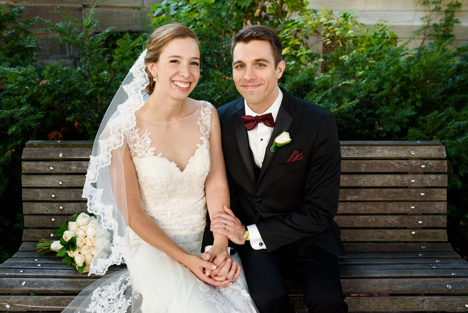 Wedding couple sitting on bench in front of church