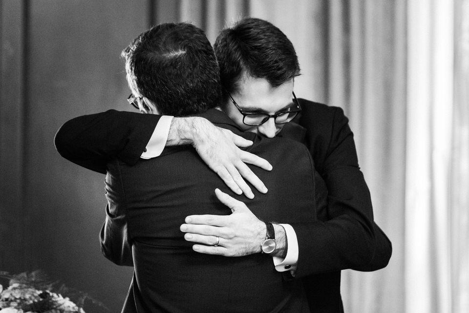 Groom hugging godfather