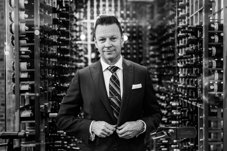 Groom adjusting his suit in front of wine cellar