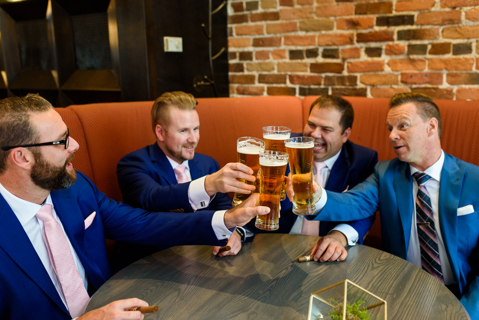Groomsmen clinking their beer glasses at Hotel Nelligan
