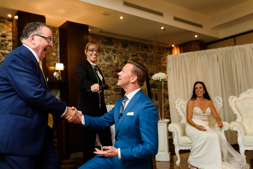 Groom on one knee before bride's father