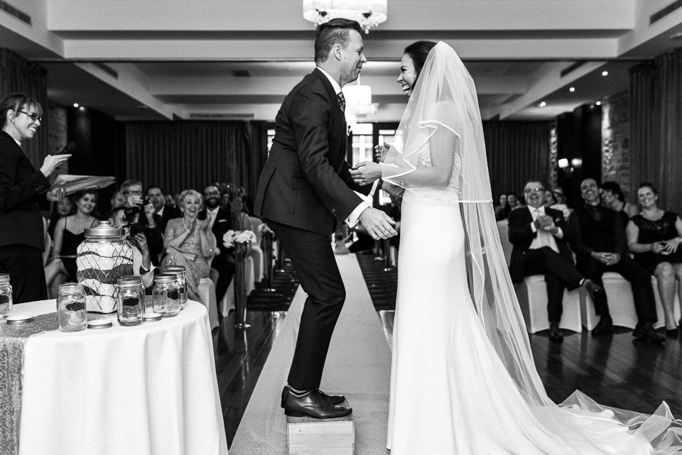 Groom standing on apple box to reach bride