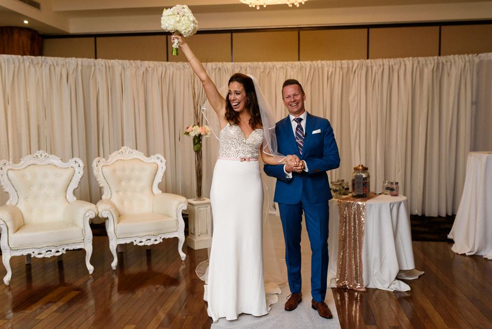 Triumphant bride raising bouquet