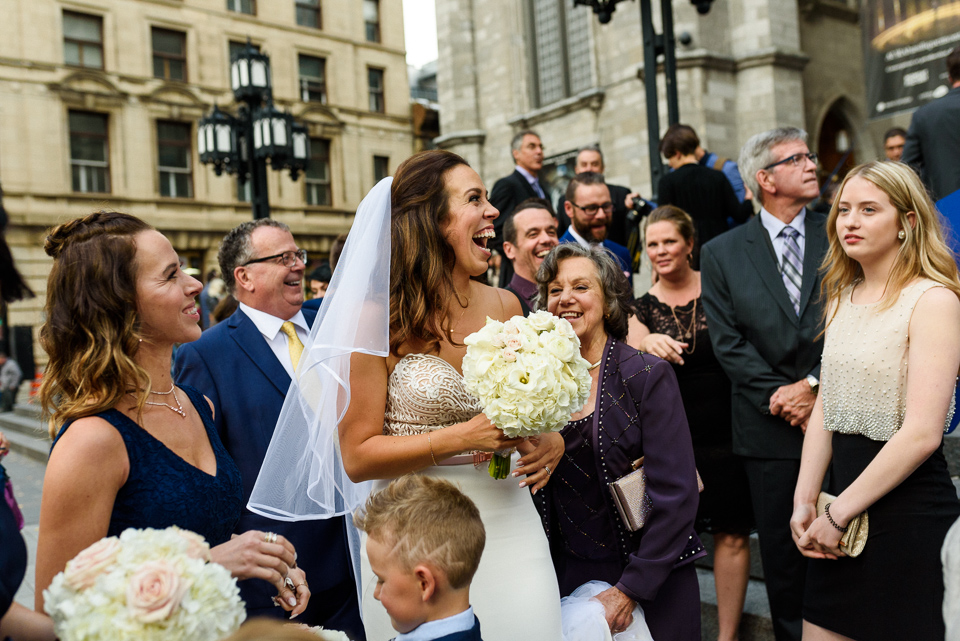 Happy bride and wedding guests in front of Notre-Dame Basilica