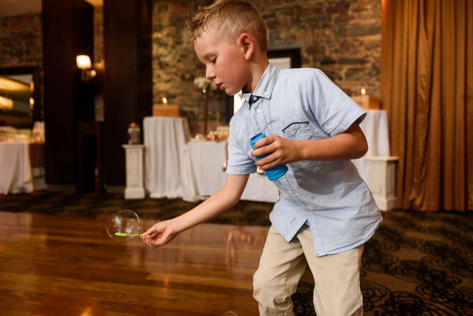 Kid playing with bubbles at Hotel Nelligan wedding reception