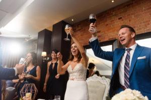 Wedding couple raising glasses in toast