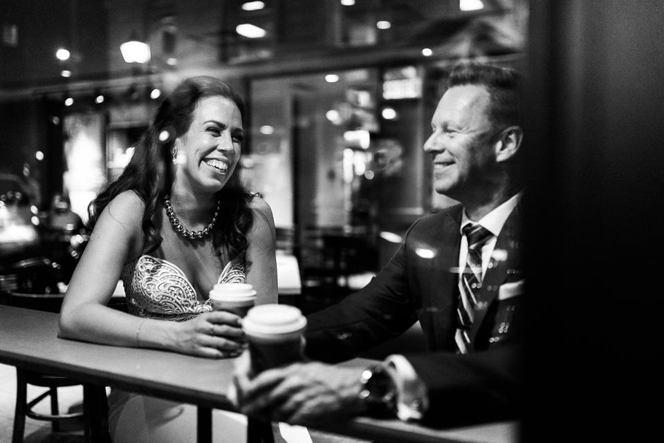 Night photo of bride and groom through window of coffee shop