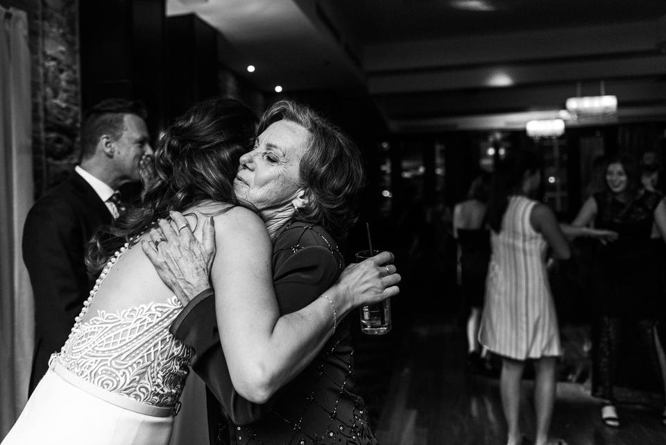 Bride hugging her mother at wedding reception