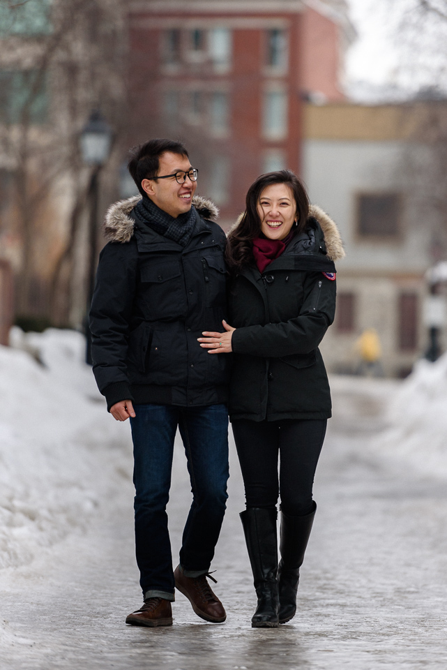 Winter engagement photo of couple walking on icy path in Old Montreal