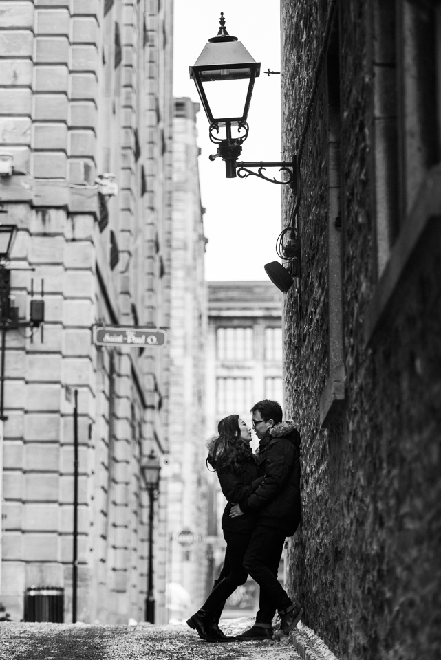 Black and white engagement photo in Old Montreal alleyway