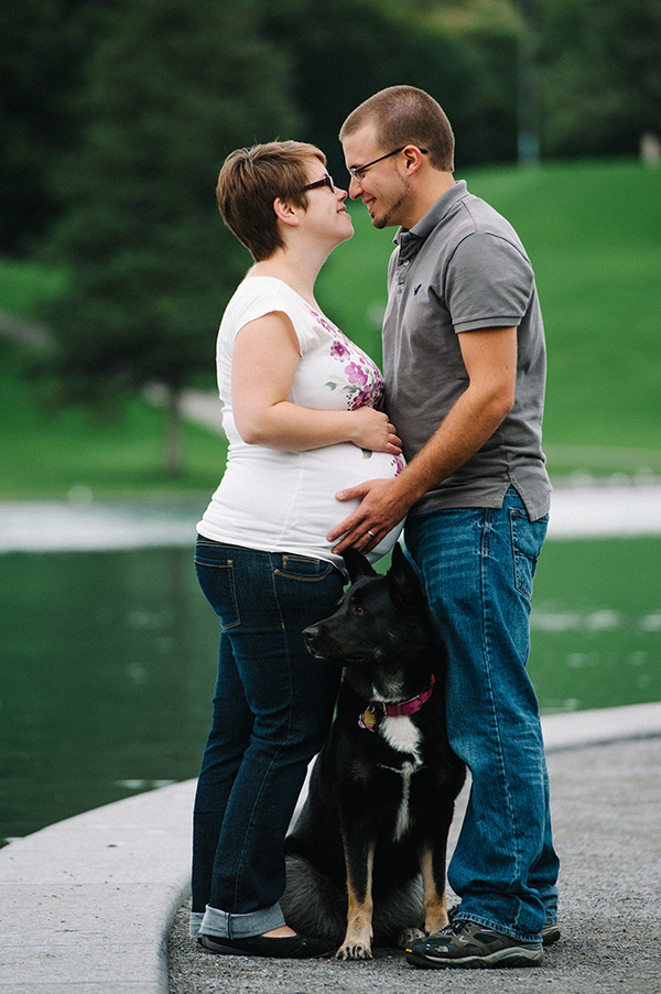 Pregnant woman and man embracing with pet dog