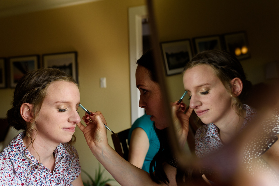 Reflection photo of bride getting makeup done
