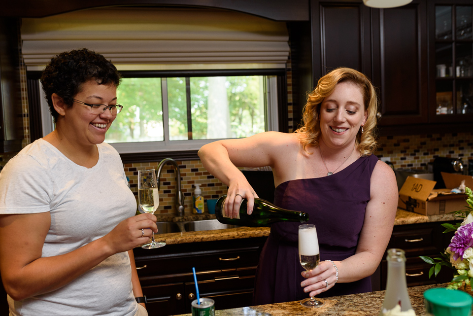 Women pouring champagne in kitchen