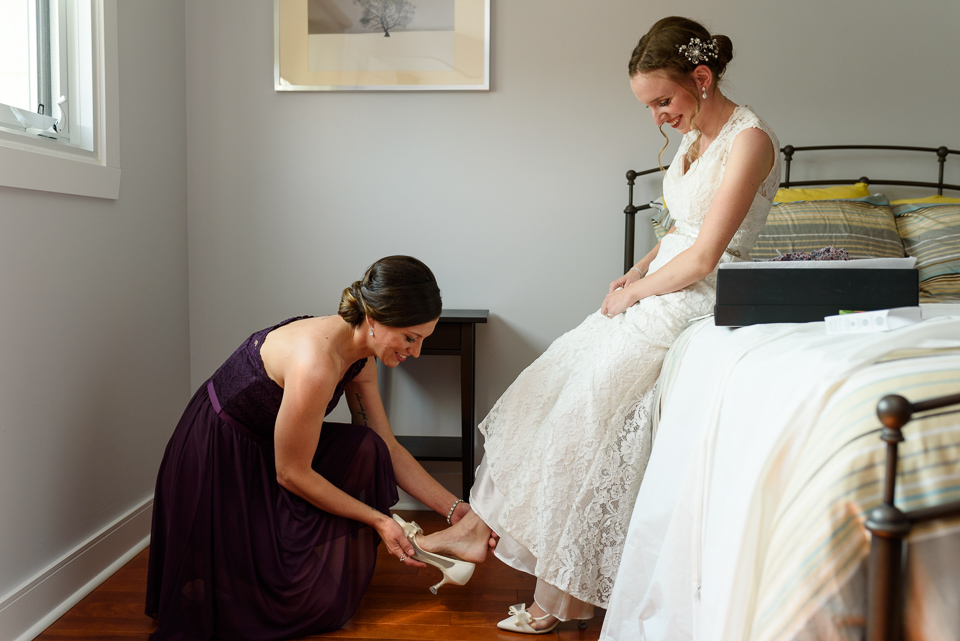 Friend putting shoe on bride