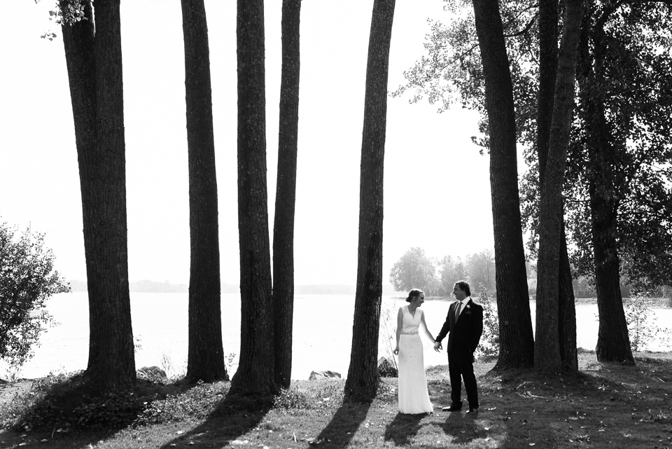 Bride and groom standing on the riverside in a row of tall trees