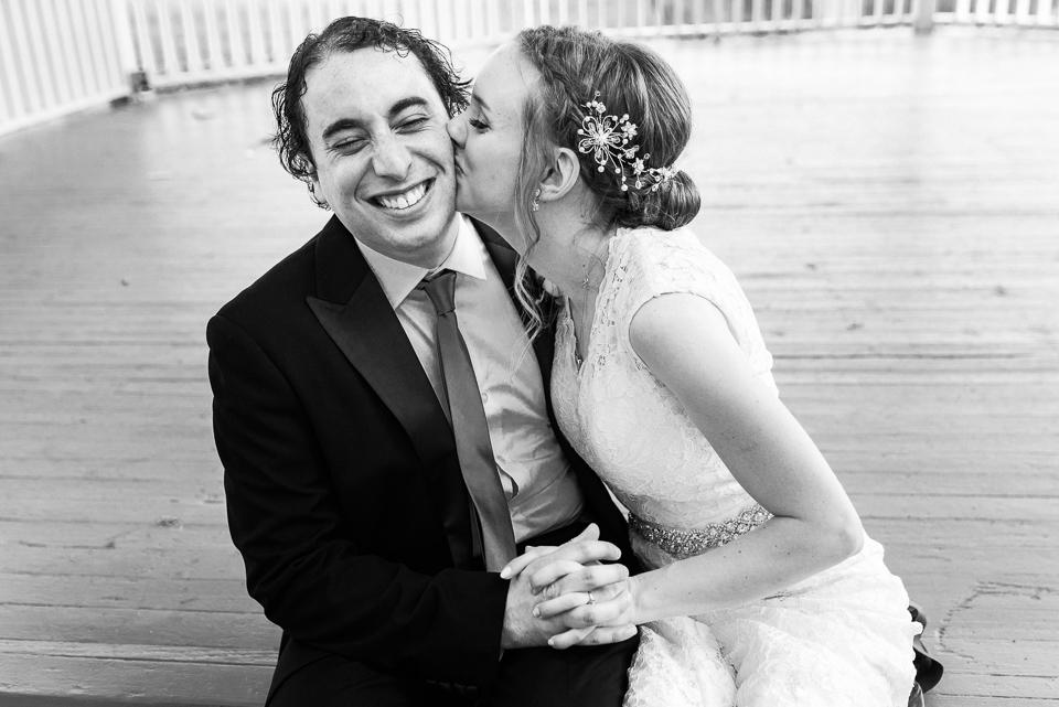 Bride kissing groom's cheek in gazebo