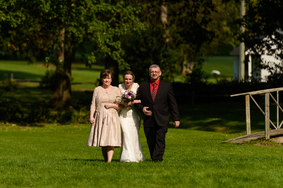 Bride and parents walking to wedding ceremony