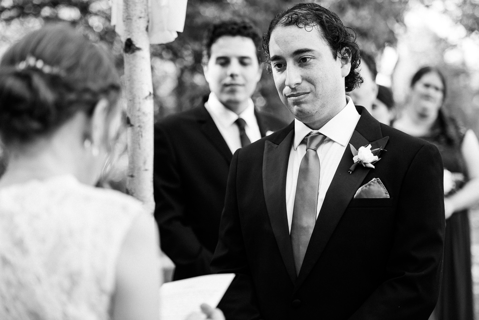 Groom looking at bride during outdoor wedding ceremony