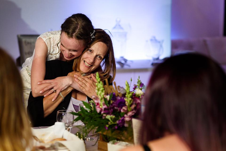 bride giving hug to wedding guest