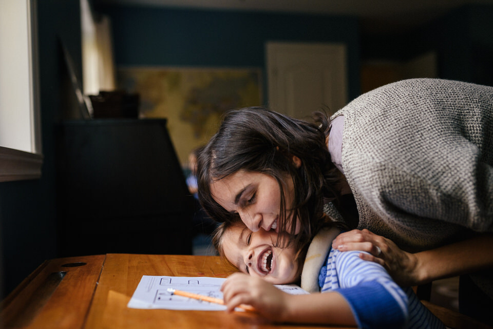 Mom hugging child as they do their homework laughing