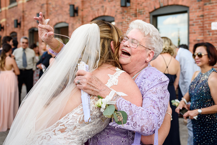 Reportage-style wedding photo of grandmother hugging bride