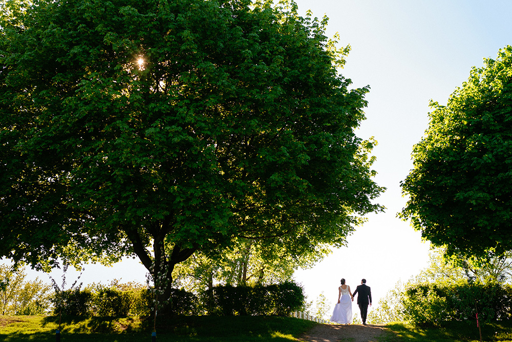 Romantic wedding photo of bride and groom walking away over a hill in the countryside