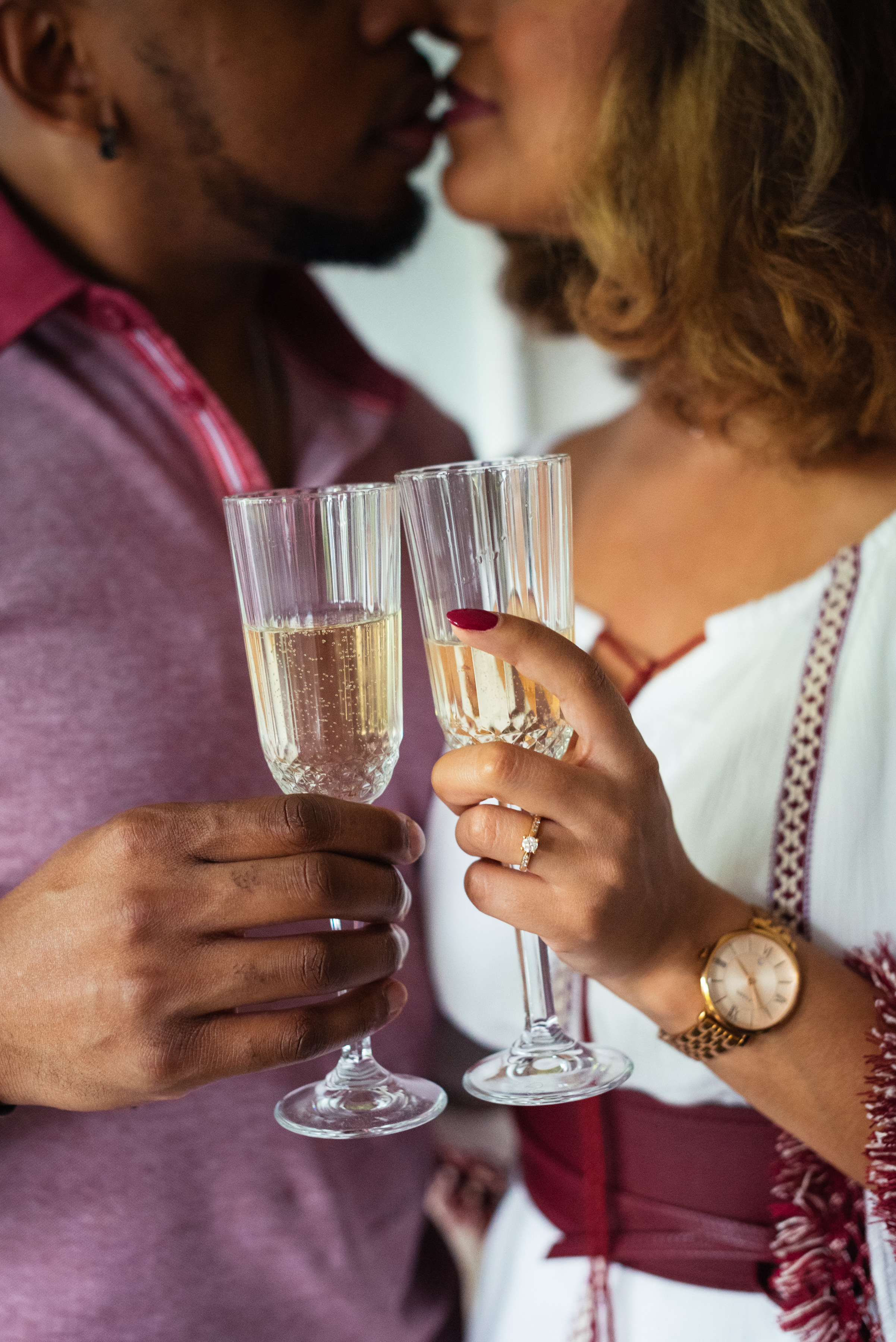 Closeup of champagne flutes with engaged couple