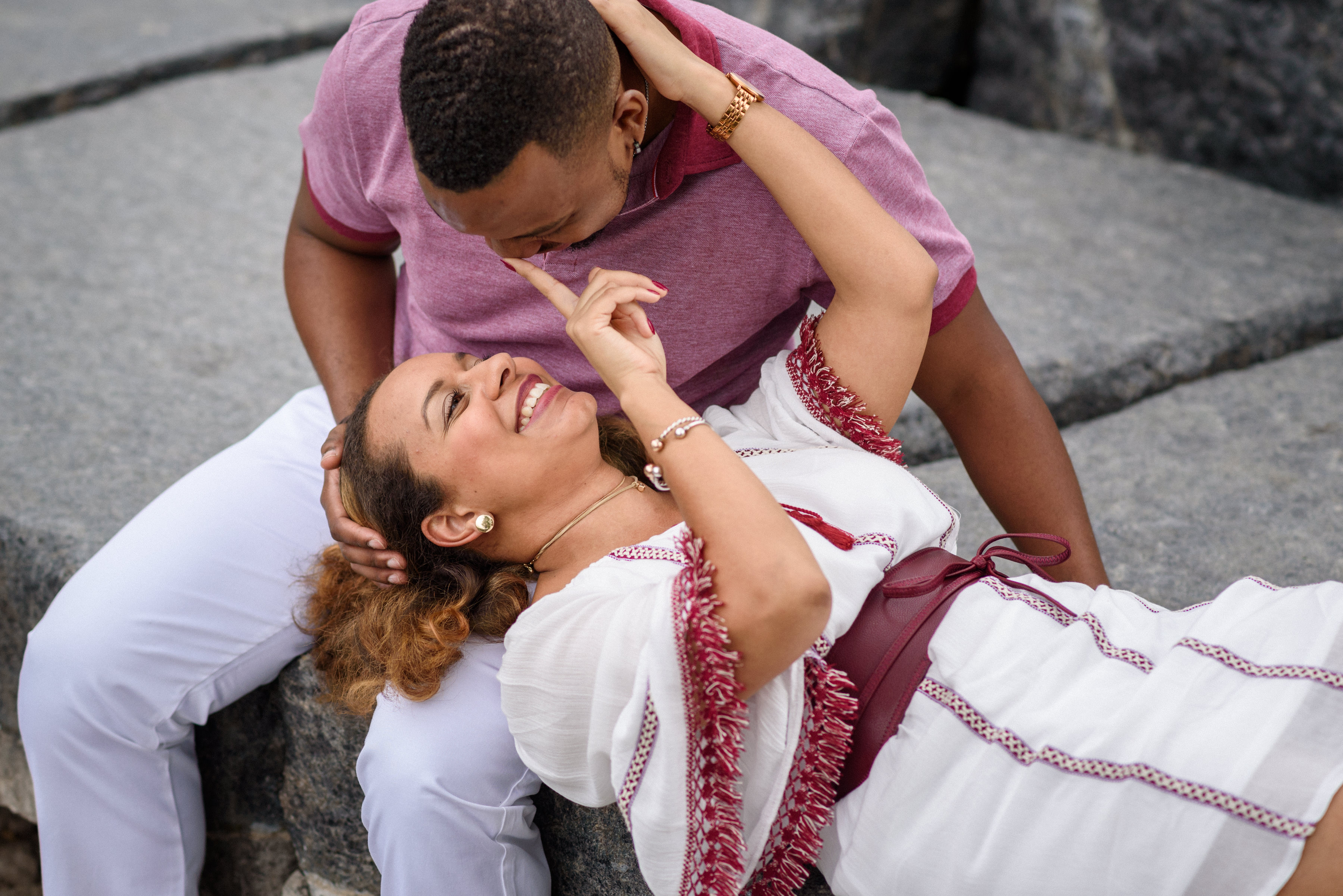 woman lying in man's lap and poking his nose