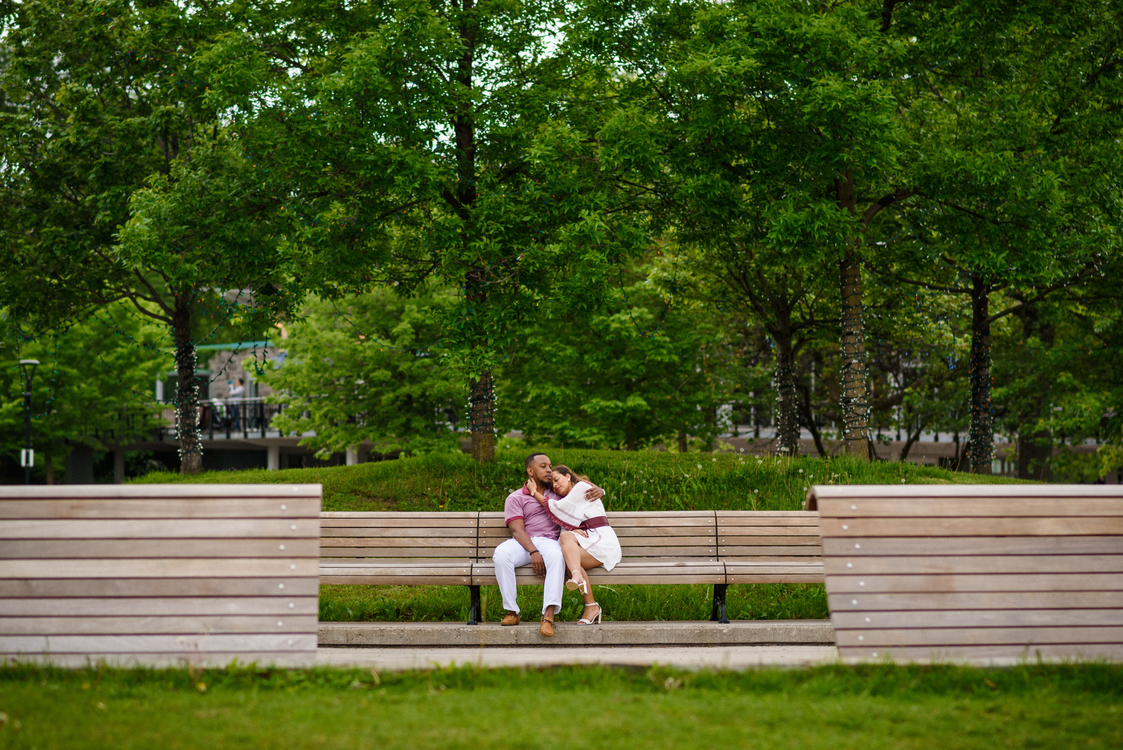 Engaged couple sitting on benches in Mount Royal Park