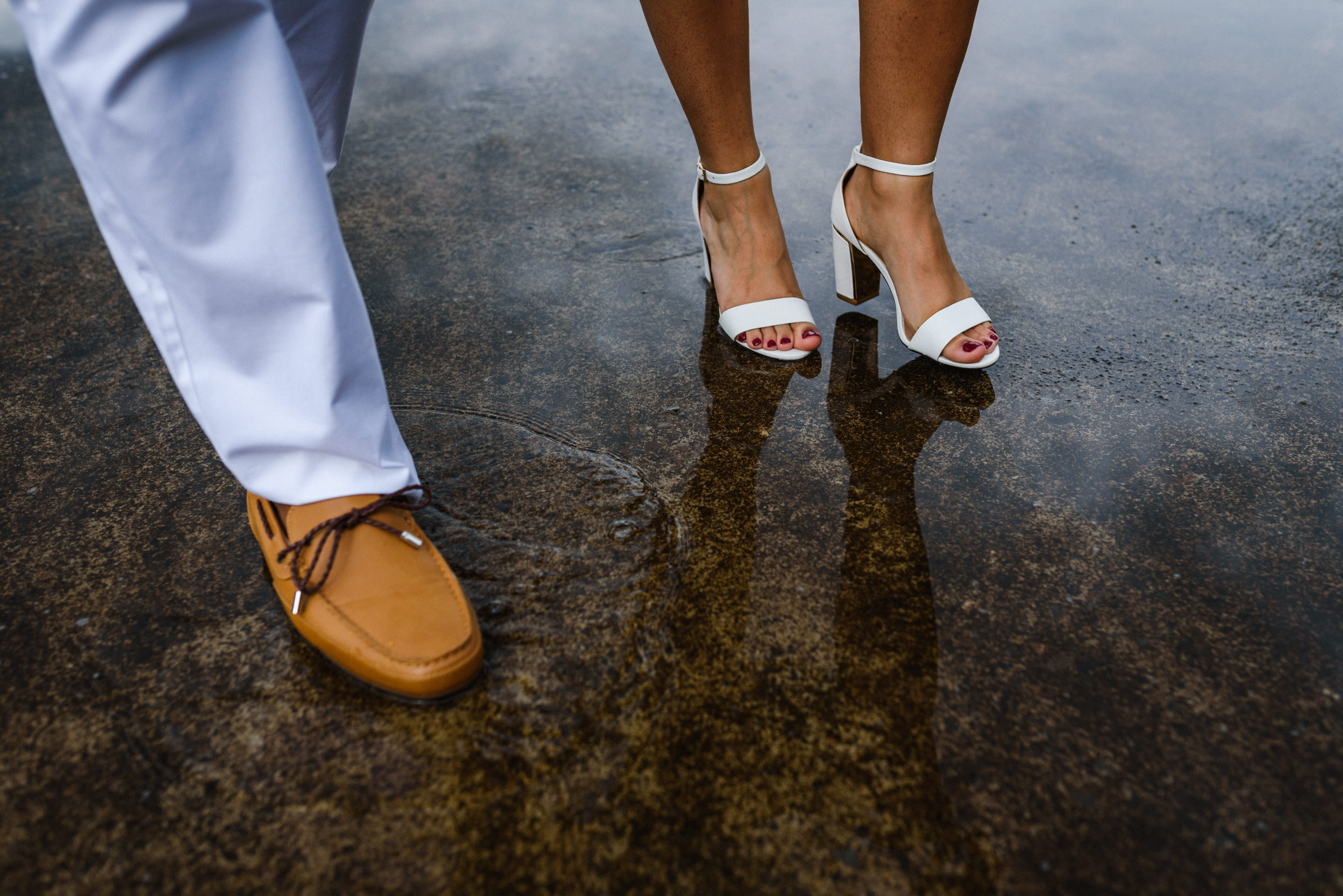 Close up of man and women's feet walking through puddle