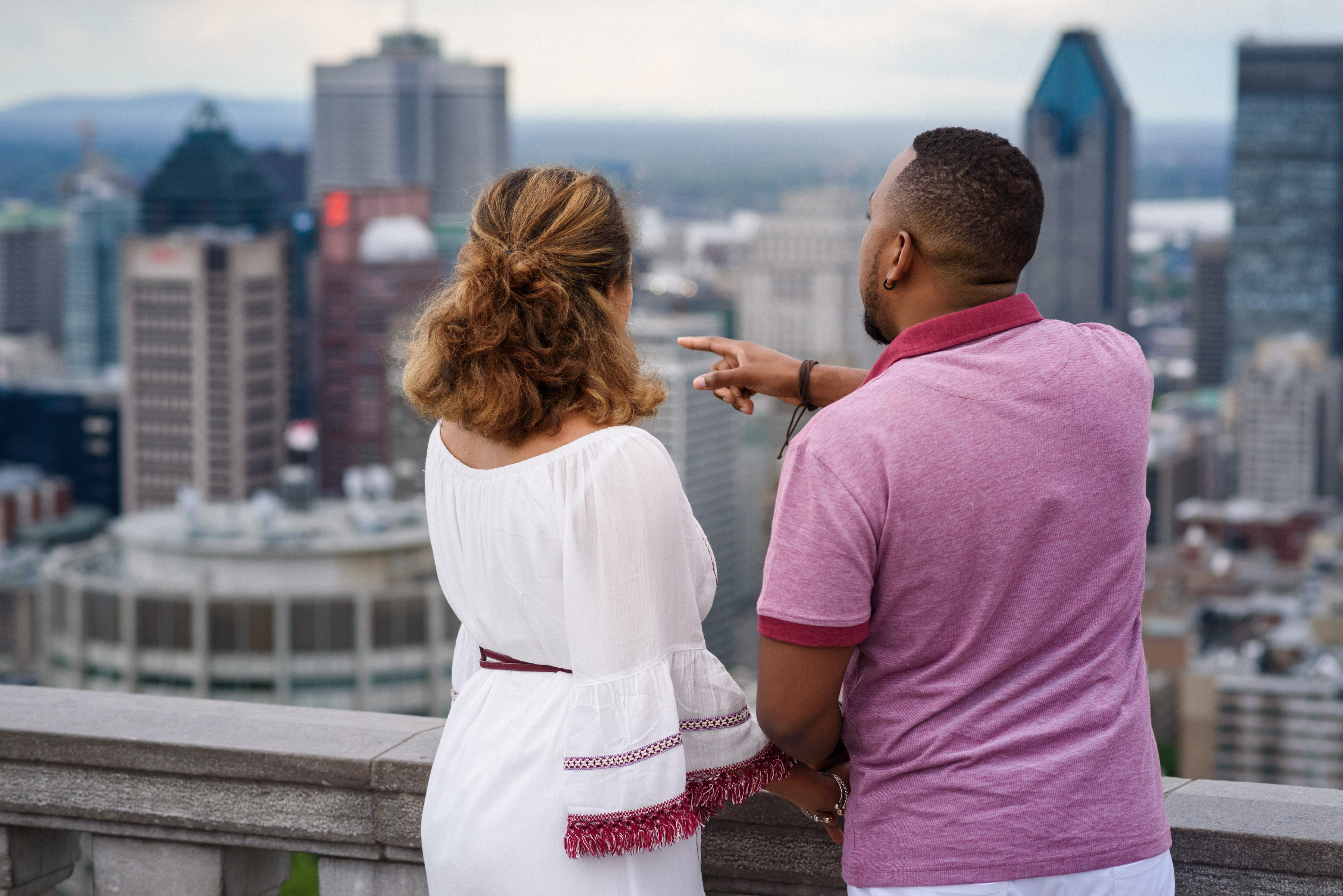 Man pointing as woman enjoys view from Mount Royal Park lookout