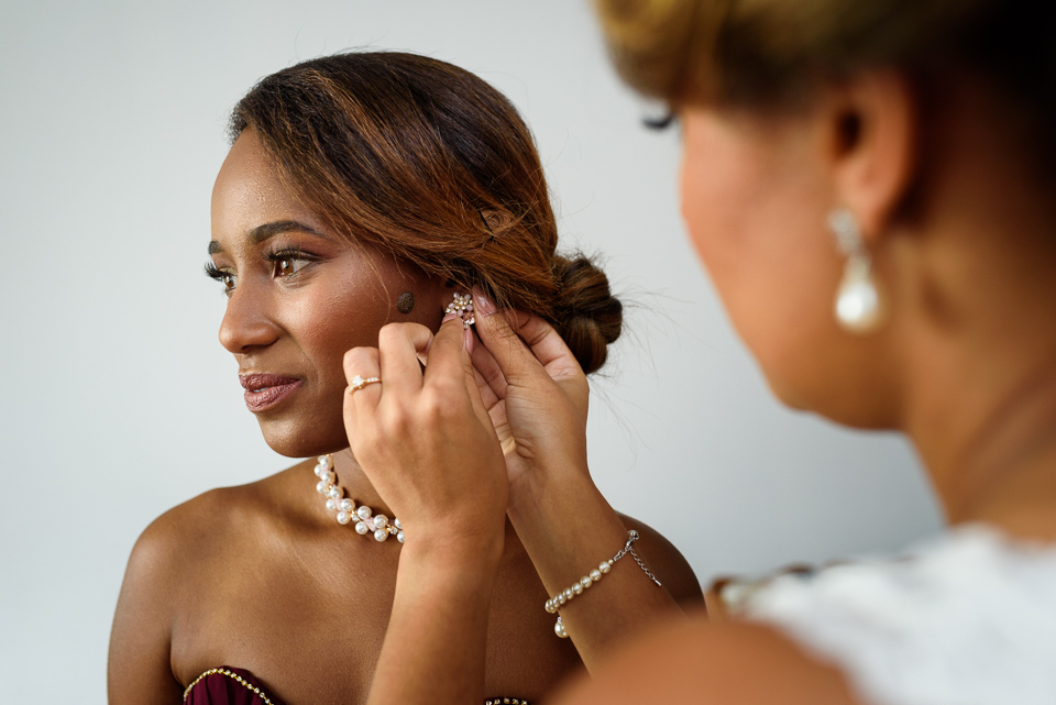 Bride putting her maid of honor's earring on