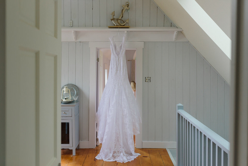 Bride wedding dress hanging up in a pale cottage doorway