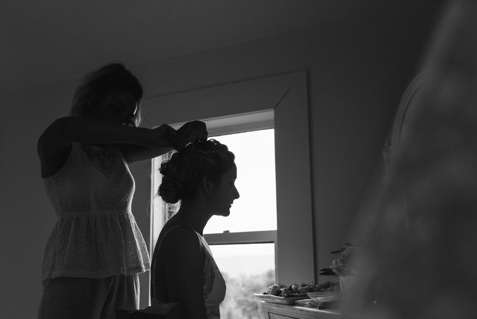 Bride silhouetted against window as she gets her wedding hair done