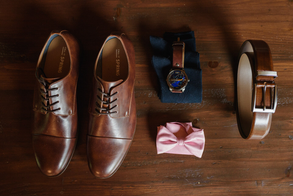 Flat lay photo of groom's accessories on wooden floor (shoes, bowtie, watch, socks and belt)