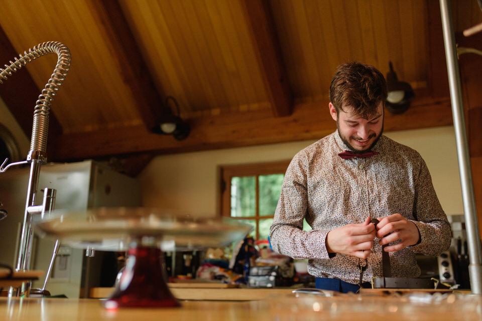 Groomsman fixing a broken suspender