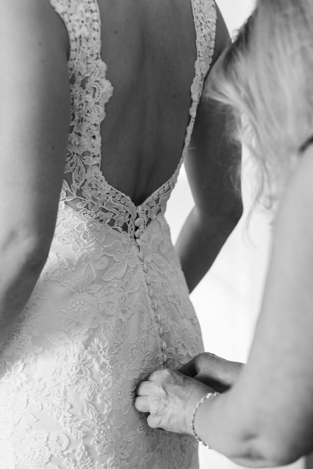 Mom buttoning up her daughter's wedding dress