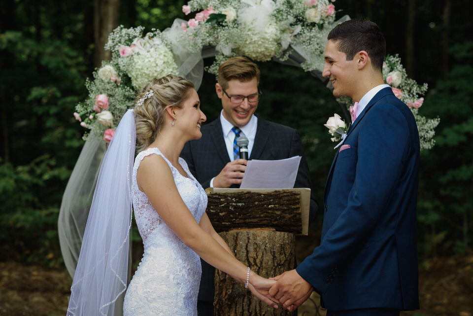 Rustic wedding ceremony in front of floral arch