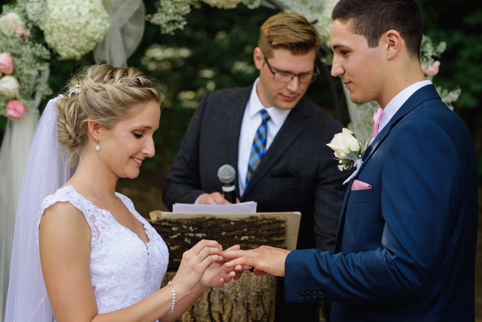 Bride putting ring on groom at rustic wedding